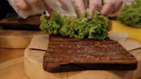 Cocinar un bocadillo en la cocina Primer del pan negro frito enyesado con la salsa, en la cual miente una hoja verde de la lechug almacen de video