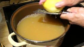 Cocinar un más viejo atasco de las cabezas de flor de la baya fabricación de la peladura de fruta del limón en un pote con el zum almacen de metraje de vídeo