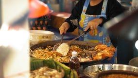 Cocinar a un tailandés delicioso del cojín en un wok grande, cámara lenta Cocinero que cocina la comida asiática de la calle en e almacen de video