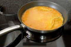 Cocinar una tortilla de huevos que moquea agradable Imagen de archivo
