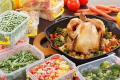 Cocinar verduras congeladas y la comida asada del pollo Imagenes de archivo
