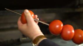 Cocinar verduras en un fuego abierto Comida campestre en el aire, comida, disfrute Tomates en el primer del fuego almacen de metraje de vídeo