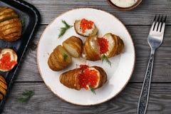 Cocinarse, las patatas cocidas con la salsa holandesa y el caviar rojo Foto de archivo