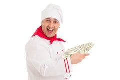 Cocine al hombre que sostiene la fan de los dólares que llevan el uniforme del blanco Foto de archivo libre de regalías