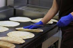 Cocine con los guantes azules del látex como cocina la especialidad italiana llamada Imagenes de archivo