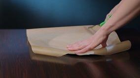 Cocine cortar una sección del papel de la hornada con las tijeras almacen de metraje de vídeo