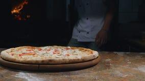 Cocine en el delantal que saca la pizza caliente y caliente del horno almacen de video