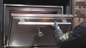 Cocine en guantes de goma negros pone el pedazo de carne en horno con el fuego usando cierre de la herramienta del metal para arr almacen de metraje de vídeo