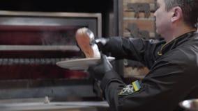 Cocine en guantes de goma negros pone el pedazo de salmones en cierre del horno Los pescados frescos del lugar del cocinero dentr metrajes