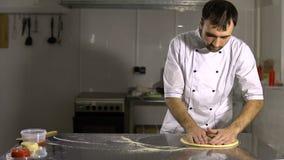 Cocine en la cocina que prepara la pasta de la pizza El hombre prepara los pasteles almacen de metraje de vídeo