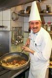 Cocine en la estufa que prepara la comida en la cocina Imagen de archivo libre de regalías