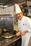Cocine en la estufa que prepara la comida en la cocina Imagenes de archivo