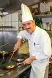 Cocine en la estufa que prepara la comida en la cocina Fotos de archivo libres de regalías