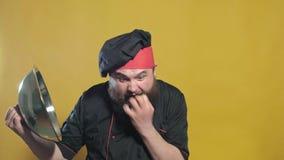 Cocine en un traje negro en un fondo amarillo almacen de metraje de vídeo