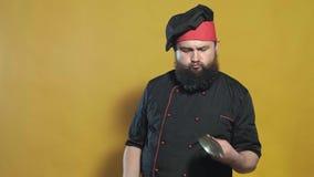 Cocine en un traje negro en un fondo amarillo almacen de video