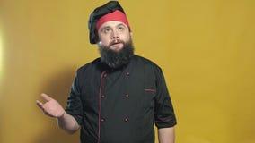 Cocine en un traje negro en un fondo amarillo metrajes