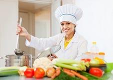 Cocine en uniforme con la cucharón en la cocina comercial Imagen de archivo libre de regalías