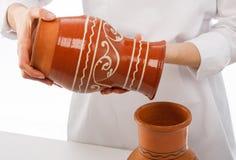 Cocine la colada algo en el jarro de la arcilla Fotografía de archivo