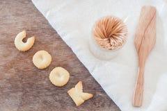 Cocine la galleta del alfabeto con la galleta del alfabeto de las pastas del fusili en la madera Foto de archivo