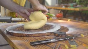 Cocine la mano que hace la pasta para cocinar las pastas en fondo de la comida Manos masculinas que amasan la pasta en el tablero almacen de metraje de vídeo