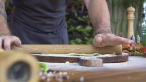 Cocine la pasta fina rodante con el rodillo para la empanada en el tablero de madera Procese la pasta de levadura rodante con el  almacen de metraje de vídeo