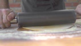 Cocine la pasta fina rodante con el rodillo para la pizza hecha en casa en el tablero de madera Procese la pasta de levadura roda metrajes