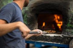 Cocine la pizza que cuece en un horno de piedra tradicional imagenes de archivo