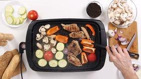 Cocine la preparación de la carne y de verduras de cerdo en una parrilla en la cocina almacen de metraje de vídeo