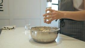 Cocine las manos de la mujer añaden el girasol o el aceite de oliva a los pasteles almacen de video