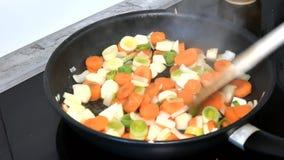 Cocine las verduras de las fritadas, revolviéndolas lentamente almacen de video
