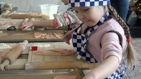 Cocine los casquillos y los delantales, rodados encima de sus figuras del corte de las mangas en la pasta amarga para las galleta almacen de video
