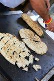 cocine mientras que cuece el piadina en la placa caliente Imagen de archivo libre de regalías