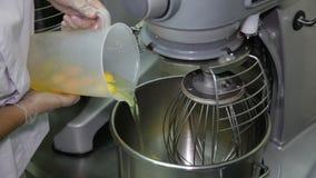 Cocine a Pouring los huevos en el mezclador metrajes