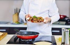 Cocine sostener la placa con la comida en gesto que da la bienvenida Imágenes de archivo libres de regalías
