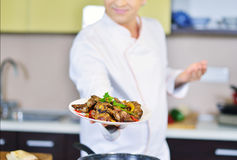 Cocine sostener la placa con la comida en gesto que da la bienvenida Foto de archivo libre de regalías