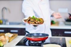 Cocine sostener la placa con la comida en gesto que da la bienvenida Fotos de archivo