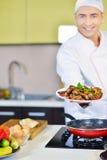 Cocine sostener la placa con la comida en gesto que da la bienvenida Fotografía de archivo libre de regalías