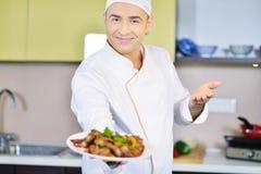Cocine sostener la placa con la comida en gesto que da la bienvenida Fotos de archivo libres de regalías