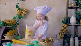 Cocinero adorable de la muchacha del niño en la cocina que juega con la harina
