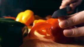 Cocinero aficionado que corta la pimienta dulce roja jugosa Concepto sano de la consumición clip de la cámara lenta 4K almacen de metraje de vídeo