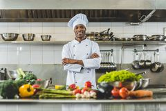 cocinero afroamericano hermoso que se coloca en la cocina del restaurante con los brazos cruzados y la mirada imagenes de archivo