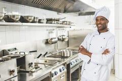 cocinero afroamericano sonriente que se coloca con los brazos cruzados y la mirada de la cámara foto de archivo libre de regalías