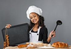 Cocinero alegre de la muchacha que lleva a cabo el tablero del menú Imagenes de archivo