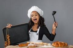 Cocinero alegre de la muchacha que lleva a cabo el tablero del menú Imágenes de archivo libres de regalías