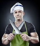 Cocinero amenazador del hombre que sostiene dos cuchillos afilados Imágenes de archivo libres de regalías