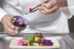 Cocinero Arranging Edible Flowers en la ensalada Imagen de archivo libre de regalías