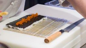 Cocinero asiático en caviar que pone uniforme del blanco encendido almacen de metraje de vídeo