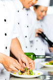 Cocinero asiático en cocinar de la cocina del restaurante fotos de archivo libres de regalías