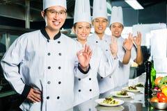 Cocinero asiático en cocinar de la cocina del restaurante imagen de archivo libre de regalías