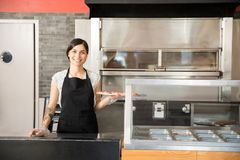 Cocinero atractivo de la mujer que muestra la pizza sabrosa grande mientras que coloca el beh imágenes de archivo libres de regalías